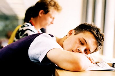 side profile of a male student asleep on his desk in class